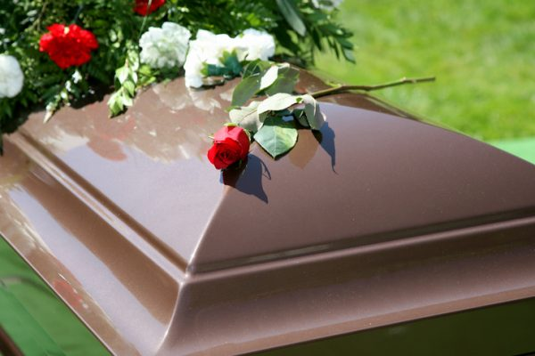 A single brown casket with a spray of flowers.
